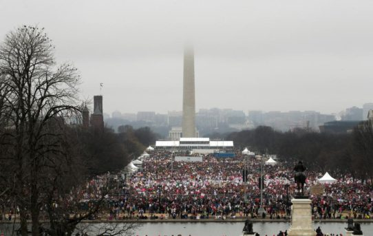 The top of the Washington Monument is shrouded in clouds as people pack the National Mall for the Women's March in Washington. REUTERS/Jonathan Ernst